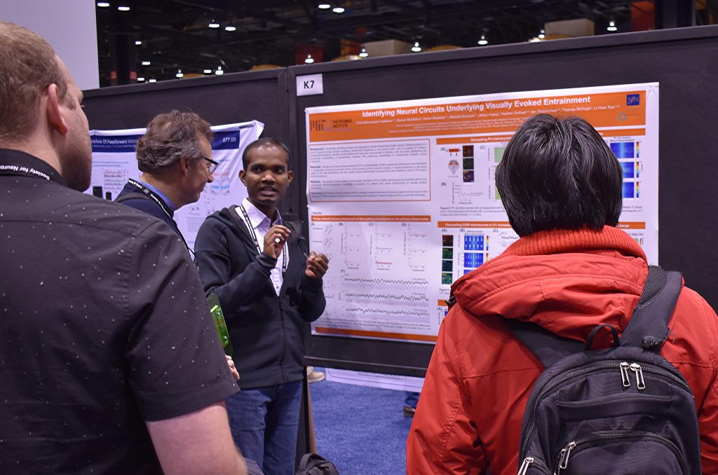 Chinna Adaikkan stands before a research poster and talks to two onlookers.