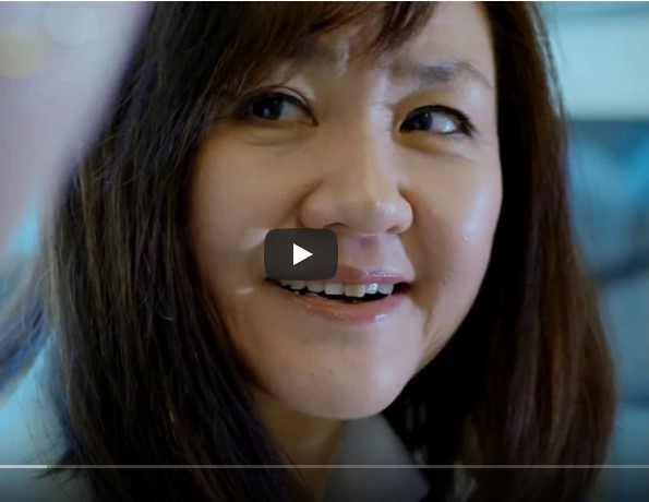 Li-Huei Tsai smiles in a picture with a video play button superposed in the foreground